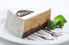 Sahnekuchen auf weißer Platte, Schokoladenbelag mit Kuchen, Konditorei, süßes Törtchen mit tadellosem Blatt, Shop, Kakaocreme Lizenzfreie Stockfotografie