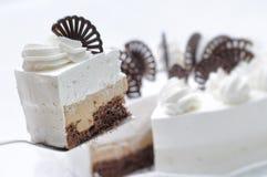 Sahnekuchen auf weißer Platte, Schokoladendekoration mit Kuchen, Konditorei, süßes Törtchen mit Kakaocreme Stockbilder