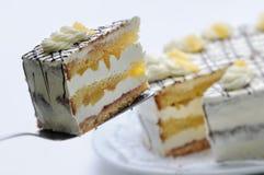 Sahnekuchen mit Birnen und Schokoladenbelag auf Metalllöffel, Geburtstagskuchen auf weißer Platte, Konditorei, Fotografie für Sho Lizenzfreie Stockbilder