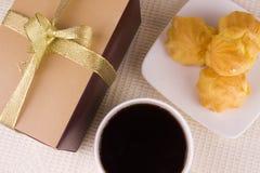 Sahnekuchen mit Kaffee und Geschenk lizenzfreie stockbilder