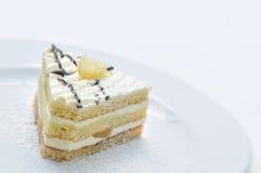 Sahnekuchen mit Pulverzucker auf weißer Platte, Süßspeise, Konditorei, Shop, Kakaopulver Lizenzfreie Stockfotografie