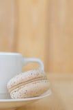 Sahnemakrone, macaron mit Schale auf hölzernem Hintergrund Lizenzfreie Stockfotos