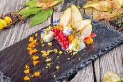 Sahnenachtisch des exklusiven Herbstes mit Birnen, Korinthen und Pistazien auf dem schwarzen Brett, verziert mit den Blumenblumen Stockfotografie