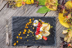 Sahnenachtisch des exklusiven Herbstes mit Birnen, Korinthen und Pistazien auf dem schwarzen Brett, verziert mit den Blumenblumen Stockbild