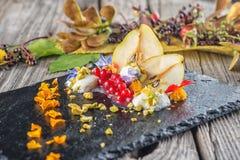 Sahnenachtisch des exklusiven Herbstes mit Birnen, Korinthen und Pistazien auf dem schwarzen Brett, verziert mit den Blumenblumen Lizenzfreie Stockbilder