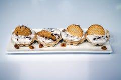 Sahneplätzchen auf der weißen quadratischen Platte lizenzfreies stockfoto