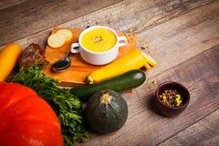Sahnesuppe des Kürbises diente mit gebratenen Samen und Croutons auf einem hölzernen Hintergrund Chef gießt Olivenöl über frische stockbild