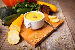 Sahnesuppe des Kürbises diente mit gebratenen Samen und Croutons auf einem hölzernen Hintergrund Chef gießt Olivenöl über frische lizenzfreies stockbild