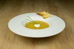 Sahnesuppe mit Toast auf Platte auf Holztisch Lizenzfreies Stockbild