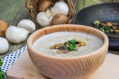 Sahnige Champignon-Suppe in der hölzernen Schüssel mit Sautéed-Champignon M Stockfotografie