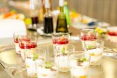 Sahnige Cupnachtische auf silberner Tellersegmentcafeteria stockbild
