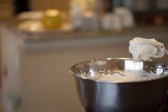Sahnige Eiweiße auf Mischer wischt über Schüssel mit Küche im Hintergrund Lizenzfreie Stockfotos