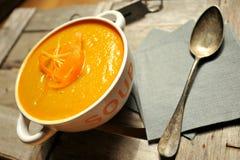 Sahnige Karottensuppe auf einem Weinlesehintergrund Lizenzfreies Stockfoto