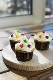 Sahnige kleine Kuchen mit Farbtropfen Stockbild