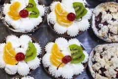 Sahnige Kuchen der Frucht mit eingemachtem Kirsch-, Orangen- und Kiwibelag stockbilder