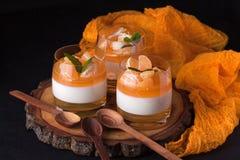 Sahniger panna Cotta mit orange Gelee in den schönen Gläsern, frische reife Mandarine auf hölzernem Abschnitt auf schwarzem Hinte Stockbild