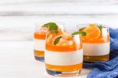 Sahniger panna Cotta mit orange Gelee in den schönen Gläsern, frische reife Mandarine, blaues Gewebe auf weißem hölzernem Hinterg Lizenzfreie Stockbilder