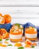 Sahniger panna Cotta mit orange Gelee in den schönen Gläsern, frische reife Mandarine, blaues Gewebe auf weißem hölzernem Hinterg Stockfotos