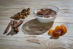 Sahniger Reispudding mit Zimtstangen, Walnüssen und getrockneten Aprikosen Lizenzfreie Stockfotografie