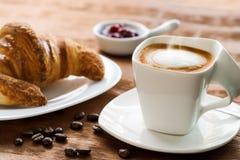 Sahniger Tasse Kaffee mit Hörnchen im Hintergrund Stockfotos