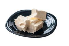 Sahniges Stück Butter auf einer schwarzen Untertasse über einem weißen Hintergrund Lizenzfreie Stockfotos
