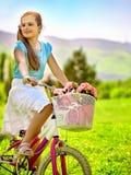 A saia branca vestindo da menina da criança monta a bicicleta no parque Fotografia de Stock