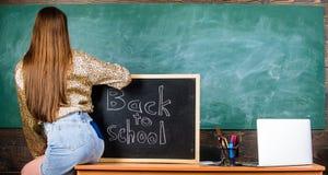 Saia da sarja de Nimes da menina que quebra regras da roupa da escola Parte traseira e estudante das nádegas perto do quadro Códi imagens de stock