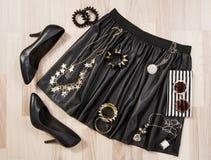 A saia e os acessórios de couro pretos arranjaram no assoalho Fotos de Stock Royalty Free