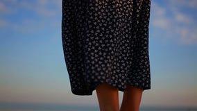 Saia fêmea modelada preto e branco longa que vibra no vento na costa de mar filme