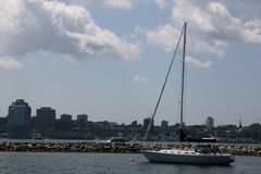 Saiboat passing by Halifax, Nova Scotia. The sailboat in the harbour as it ventures to the ocean stock photo