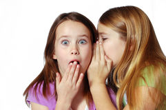 She said what?. Two girls sharing secrets and whispering Stock Images