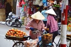 SAIGION, VIETNAM am 6. März: FrauenStraßenhändler, der große orange Frucht in Vietnam verkauft Lizenzfreie Stockbilder