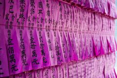 SAIGON, VIETNAM - FEB 13, 2018 - People names written on pink vintage paper in Thien Hau Pagoda, dedicated to the Chinese sea godd. People names written on pink Royalty Free Stock Image