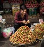 Saigon, Vietnam - June 28, 2017: Man selling rambutan fruit, Saigon, Vietnam. Man vendor selling rambutan fruit on street in Saigon Vietnam Royalty Free Stock Image
