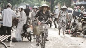 Saigon, Vietnam - June 2017: Woman on bicycle shopping on street market, Saigon, Vietnam. Royalty Free Stock Photos