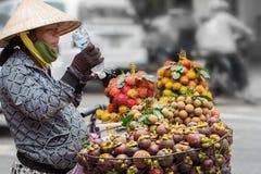 Saigon, Vietnam - June 30, 2017: Woman selling fruit on street, Saigon, Vietnam. Royalty Free Stock Images