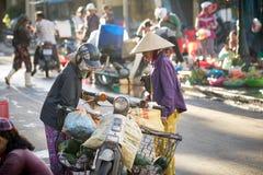 Saigon, Vietnam - June 2017: Women in conical hats bargaining on street market, Saigon, Vietnam. Women in traditional conical hats bargaining on busy asia Stock Photo