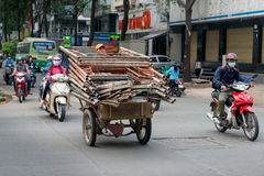 Saigon, Vietnam - Man riding overloaded scooter piled high with scaffolding Royalty Free Stock Photos