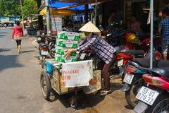 SAIGON, VIETNAM - October 16, 2014: A garbage collector collecting carton boxes on a small street, Saigon, Vietnam Royalty Free Stock Photography