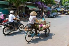 SAIGON, VIETNAME - 16 de outubro de 2014: Vendedor ambulante em uma rua pequena, Saigon, Vietname imagem de stock