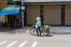 SAIGON, VIETNAME - 16 de outubro de 2014: Vendedor ambulante em uma rua pequena, Saigon, Vietname fotos de stock