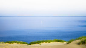 Sail Alone Far Away. Distant Single Boat Seen in the middle of calm waters Royalty Free Stock Images