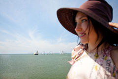 Sail away. Women with summer hat and sailboats in background Royalty Free Stock Photos