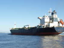 Sail away. A large cargo ship heading out to sea Stock Image