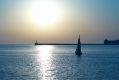 Sail boat against sunset Stock Photo