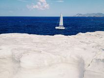 Sail boat. On the blue water of the ocean. White stone shores Stock Image