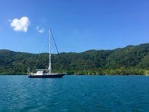 Sail boat on the calm Caribbean waters. Of Guanaja, Honduras with mountains in the background Royalty Free Stock Images