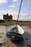 Sail Boat and Castle. A sail boat on the beach near a castle in Scotland Stock Image