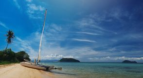Sail boat, catamaran, on tropical beach with blue water Royalty Free Stock Photos
