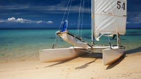 Sail boat, catamaran, on tropical beach with blue water Stock Photos